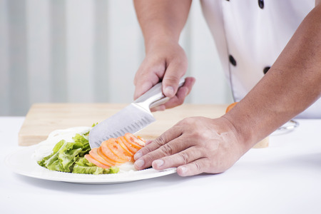Chefs hands cutting Tomato,Making Salad Concept photo