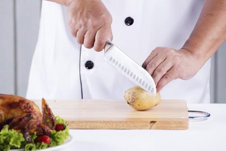 cutting bord: chef cutting potato on cutting bord