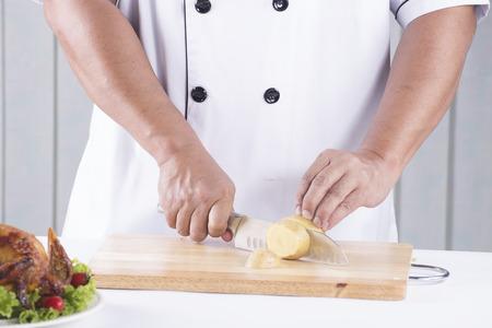cutting bord: chef cutting potato on the wooden bord