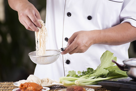 Chef holding the noodle before cooking  Cooking Noodle concept photo