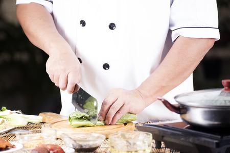chef cocinando: Cocinero que taja de verduras antes de cocinar fideos  Cocinar concepto de fideos