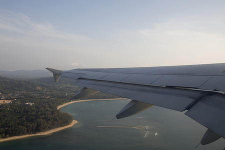 beach window: Looking from the window of the Plane, Wing of an airplane flying above the beach
