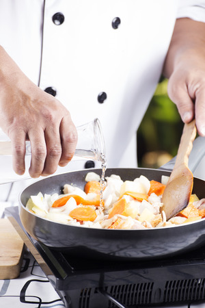 Chef pouring soup to the pan for cooking Japanese pork curry  cooking Japanese pork curry paste concept photo