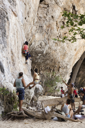 phra nang: KRABI THAILAND  MARCH 28 2015: Rock climbers climbing the wall on Phra Nang beach One of the most popular rock climbing locations in Krabi Thailand Editorial