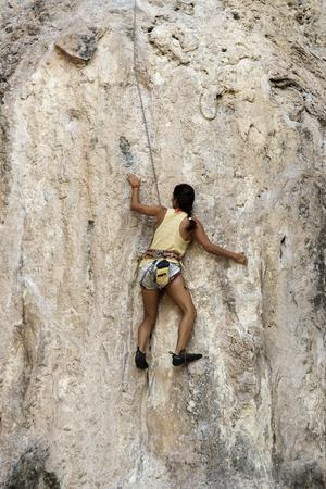 phra nang: KRABI THAILAND  MARCH 28 2015: Rock climbers climbing the wall on Phra Nang beach One of the most popular rock climbing locations in Krabi Thailand Editorial