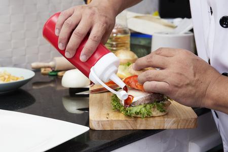 adult sandwich: Chef putting Tomato sauce to Hamburger Cooking Hamburger concept Stock Photo