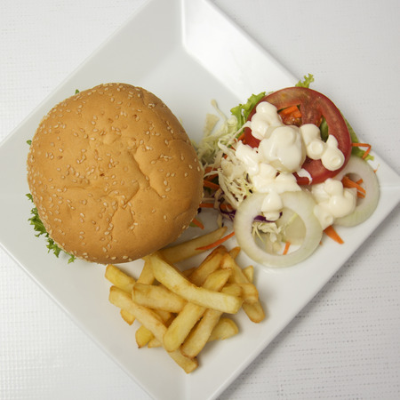 Hamburger beef ,french fries and vegetable salad on the Plate (Top view)