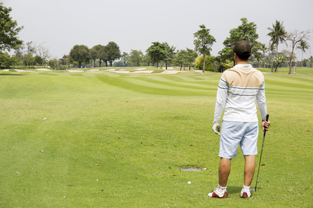 teen golf: golfista mirando colocado en la postura del golf se prepara para empujar la pelota Foto de archivo