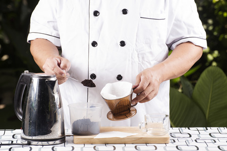 grinded: Chef putting grinded cofffe into filter cup Stock Photo