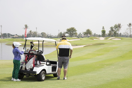 caddie: Golfer , Caddie and golf cart on the fairway waiting to hole in tropical setting