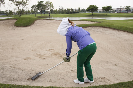 raking: Caddy raking sand by fork at golf course Stock Photo