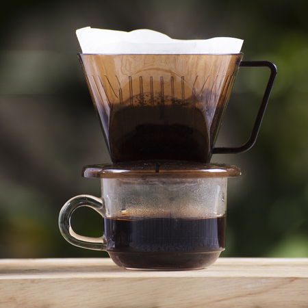 Cup of Dripping fresh hot coffee on the paper filter