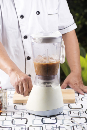 coffee blender: Chef turn on switch blender for making Coffee smoothie