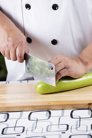 broad: Chef slicing green eggplant on wooden broad
