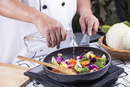 요리를 위해 냄비에 수프를 붓는 요리사 튀긴 야채 볶음