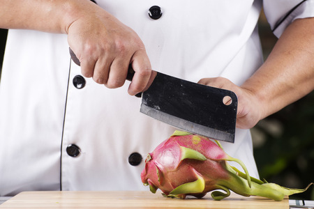 broad: Chef cutting dragon fruit on wooden broad