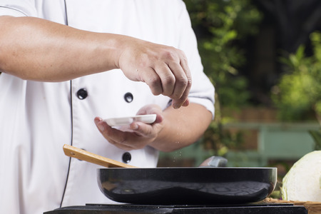 professional chef: Chef putting Salt to the pan for cooking vegetable