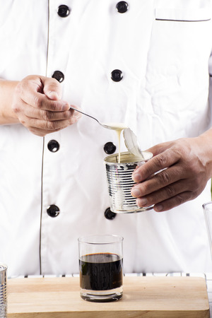 condensed: Chef putting condensed milk in to Hot coffee Stock Photo