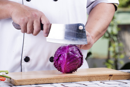 broad leaf: Chef cutting purple cabbage on wooden broad