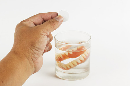 Hand holding cleaning tablets to a glass water of False Teeth  on white backgrpound