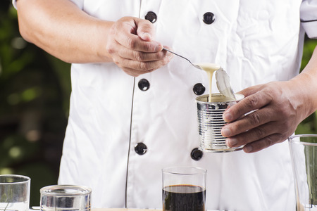 cafe bombon: Chef putting condensed milk in to Hot coffee Foto de archivo