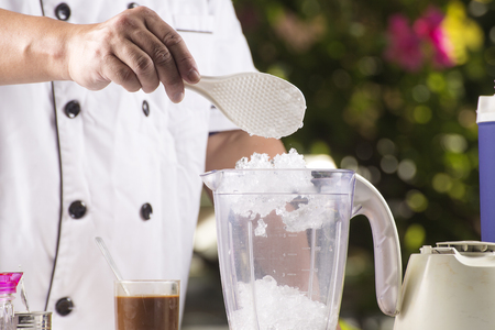 Chef putting grind ice to the Blender
