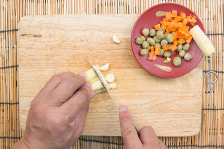 baby rice: chef slicing baby corn for cooking fired rice  cooking fire rice concept