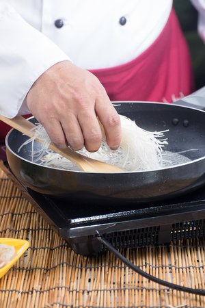 mee: Chef putting rice noodle for cooking Pad Thai   cooking Pad Thai concept