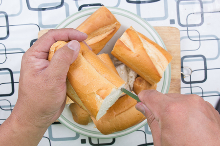 penetrate: Hand with knife penetrate bread  cooking sausage bread concept