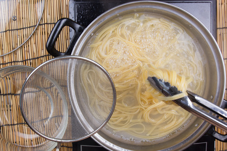 tongs: Spaghetti lifted on of cold water with tongs  cooking spaghetti concept