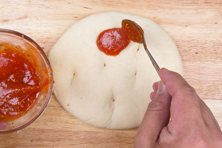 pizza crust: spreads sauce on pizza crust  cooking Pizza concept Stock Photo