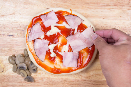 pizza crust: Putting Ham on pizza crust  cooking Pizza concept Stock Photo