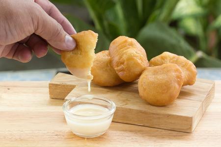 sweetened: Hand hold deep fried dough bun dip in sweetened condensed milk Stock Photo