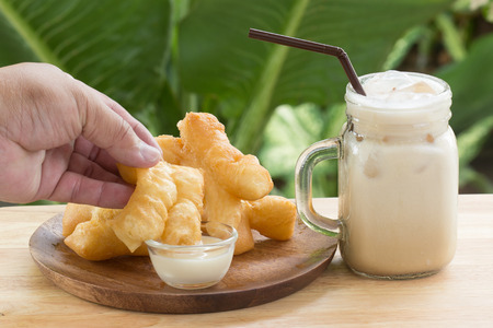 sweetened: hand holding deep fried dough stick deeping in sweetened condensed milk Stock Photo