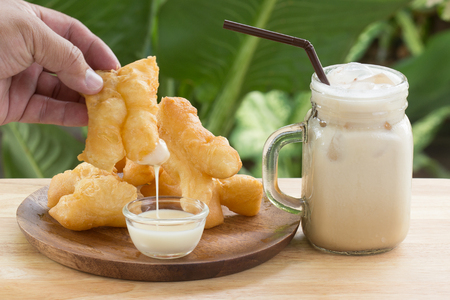 hand holding deep fried dough stick deeping in sweetened condensed milk Stock Photo