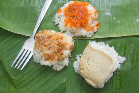 asian flavors: Thai dessert  Sticky rice topping with egg custard , Shrimp and sugar dry fish on banana leaf