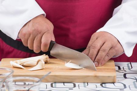 Chef slicing eringi for cooking  cooking stir fry vegetarian noodle concept