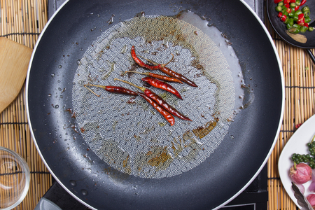 Chef frying red dried chlli in the pan  cooking spicy spaghetti concept Stock Photo