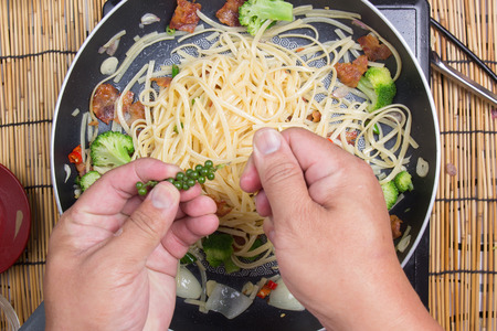 adding: Chef putting green pepper for cooking  cooking spicy spaghetti concept Stock Photo