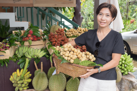 Asian woman with tropical fruit basket in the market 스톡 콘텐츠