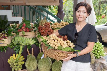 Mujer asiática con cesta de frutas tropicales en el mercado Foto de archivo - 83425430