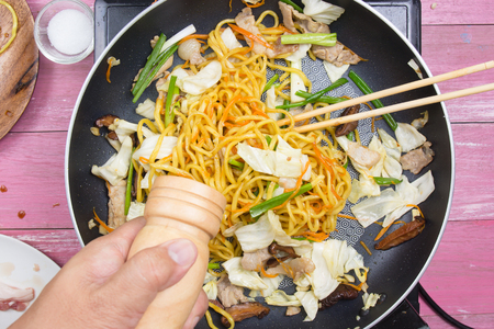 Chef put pepper for cooking Yakisoba noodle  cooking Yakisoba (Fried Japanese noodle) concept Stock Photo