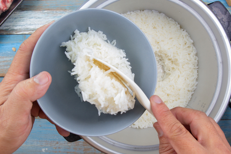 Chef put cooked rice with plastic ladle to cup in electric rice cooker 写真素材 - 102689769