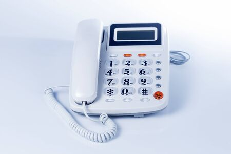 A grey telephone on the white background