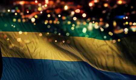 gabon: Gabon National Flag Light Night Bokeh Abstract Background Stock Photo