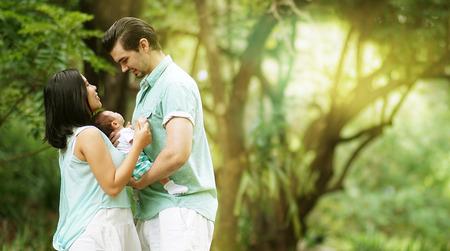 new born: Happy Mixed Race Family with New Born Baby at Park