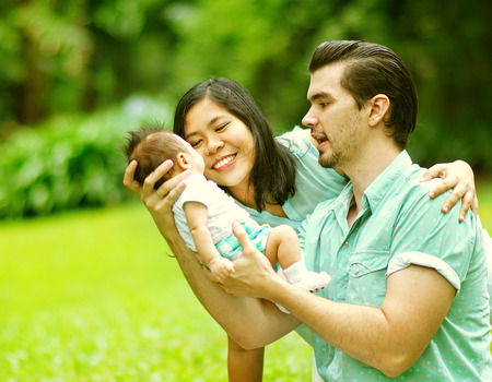 mixed race baby: Happy Mixed Race Family Playing with New Born Baby at Park