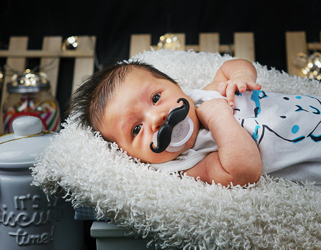 black shoes: Newborn Baby Boy Laying Down Wearing Mustache Pacifier