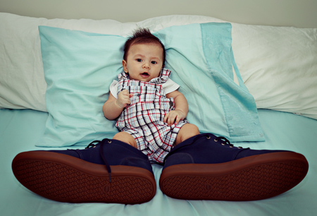 baby boys: Asian Baby Wearing Big Shoes on The Bed Stock Photo