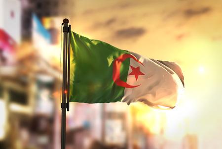 Algeria Flag Against City Blurred Background At Sunrise Backlight Stock Photo